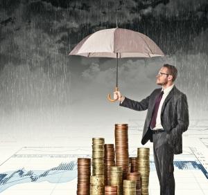 businessman cover his money with umbrella